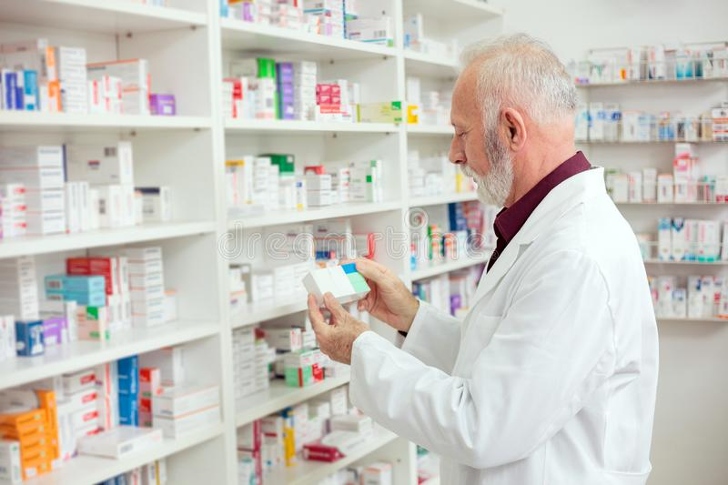 Senior male pharmacist reaching for medications from the shelf. Medicine, pharmaceutics, health care and people concept - Serious senior gray haired male royalty free stock photography