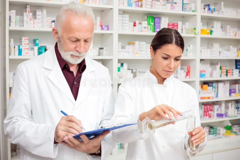 Senior male and young female pharmacists mixing chemicals in a drugstore. Medicine, pharmaceutics, health care and people concept - Serious senior male and young royalty free stock image