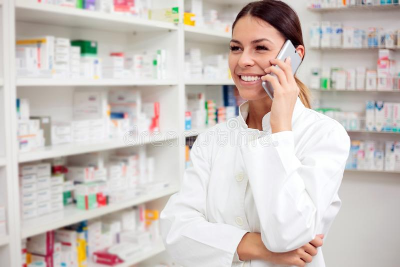 Smiling young female pharmacist talking on the phone royalty free stock photo
