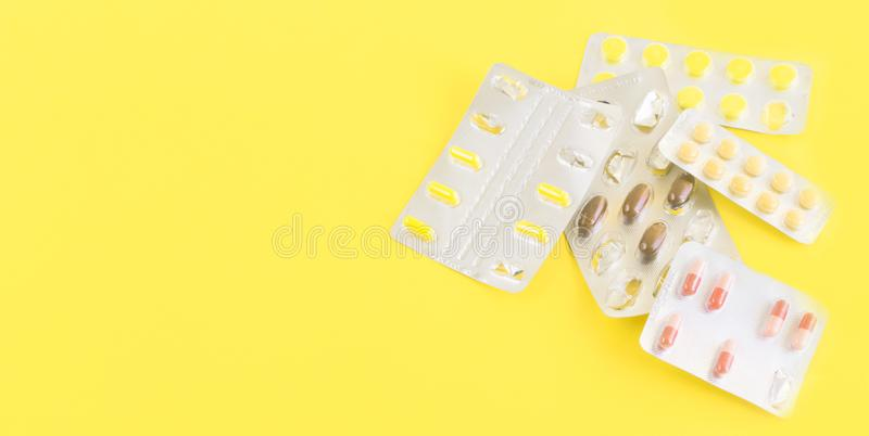 Medicine pills, capsules on yellow background.Concept of medicine.Medicines for the treatment of diseases, viruses, autumn cold. Season, beriberi, hypothermia royalty free stock images