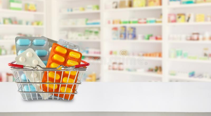 Medicine pills package in shopping basket with pharmacy blur background. Medicine pills package in shopping basket with pharmacy drugstore shelves blur royalty free stock photos