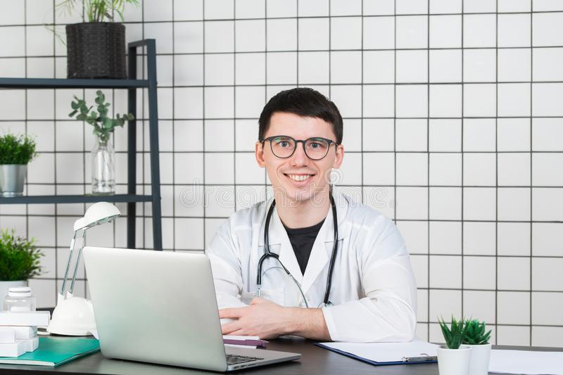 Medicine, profession, technology and people concept - smiling male doctor with laptop in medical office royalty free stock images