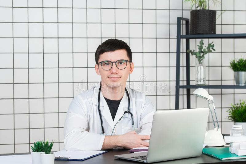 Medicine, profession, technology and people concept - smiling male doctor with laptop in medical office stock photography