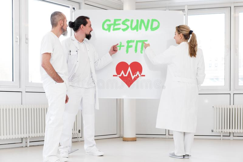 Medicine staff is standing in front of a whiteboard. On the board the german words gesund and fit which means healthy. a red heartsymbol under them. concept royalty free stock photography