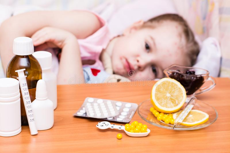 Medicine sulla tavola contro lo sfondo di un bambino in un letto con varicella fotografia stock libera da diritti