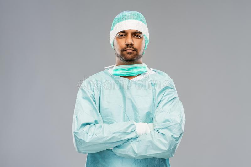 Indian male doctor or surgeon in protective wear. Medicine, surgery and people concept - indian male doctor or surgeon in protective wear over grey background royalty free stock photo