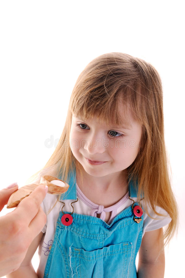 Medicine taking. Small beauty girl is taking a white tablet in wooden spoon from female hand on white background stock photography