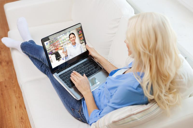 Woman having video chat with pharmacist on laptop. Medicine, technology and healthcare concept - women or customer having video chat with pharmacist on laptop stock photo