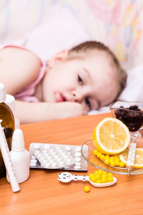 Mediciner och vitaminer på tabellen mot bakgrunden av ett barn i en säng som har vattkoppor royaltyfri bild
