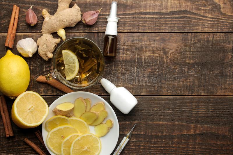 Medicines, pills, cough syrup, thermometer and folk remedies for the treatment of influenza and the common cold on a brown wooden royalty free stock photo