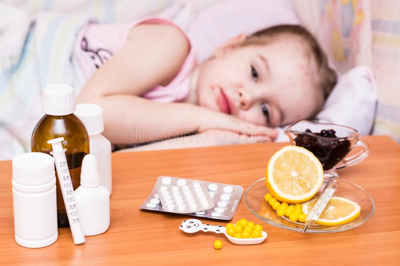Medicines and vitamins on the table against the background of a child in a bed that has chickenpox. Domestic life stock photo
