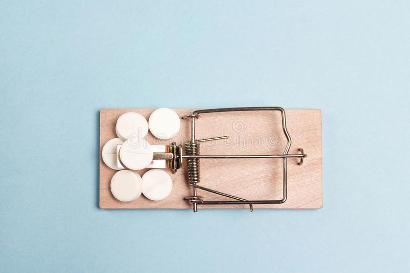 Medicines in a wooden mouse trap  on a blue background. Medicine addiction trap royalty free stock image