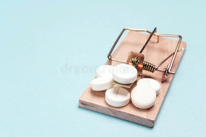 Medicines in a wooden mouse trap  on a blue background. Medicine addiction trap stock photos