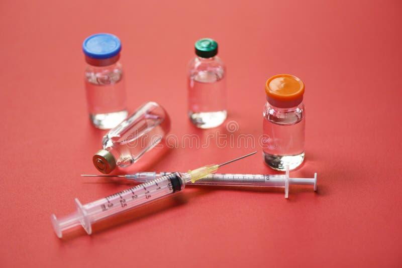 Medicinflaskexponeringsglas för injektionssprutainjektionvisare på röd bakgrund - hjälpmedel för utrustning för läkarbehandlingdr arkivfoto