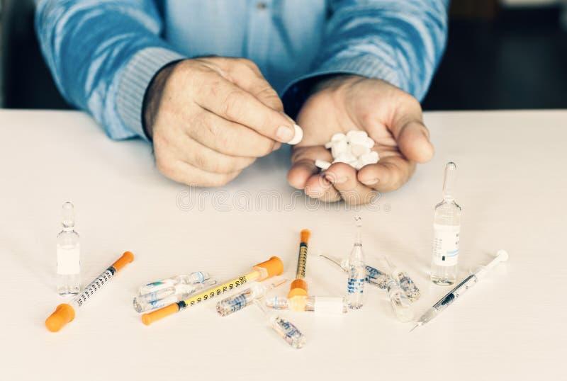 Medicinpiller eller kapslar med man'shänder på vit bakgrund med kopieringsutrymme royaltyfri fotografi
