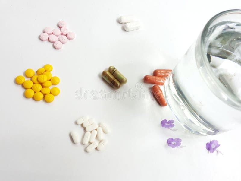 Medicinpiller och exponeringsglas av vatten arkivfoto