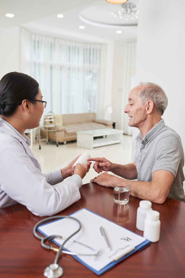 Medicinsk arbetare som talar till patienten arkivfoton