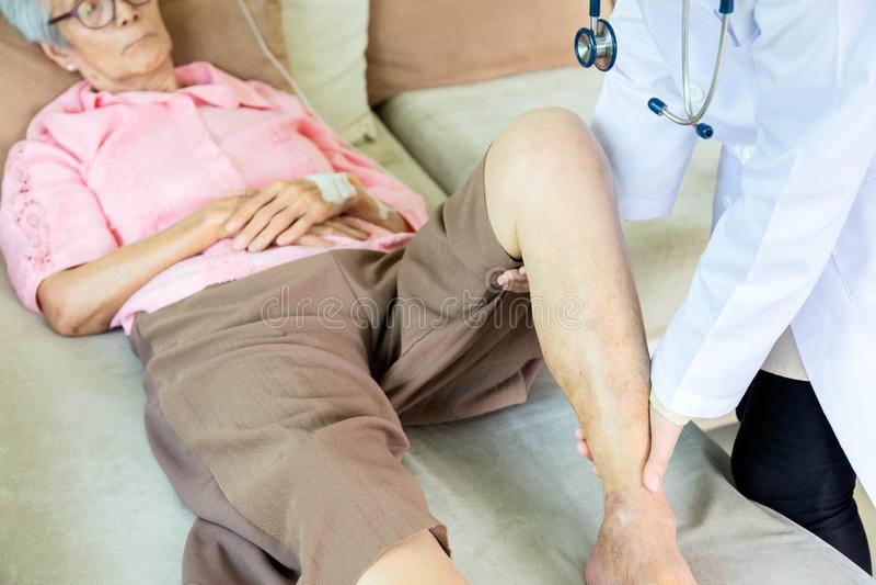 Medicinsk asiatisk doktor eller sjuksköterska som kontrollerar knäet av den höga patienten i sjukhussäng eller hemmet, äldre kvin royaltyfria foton