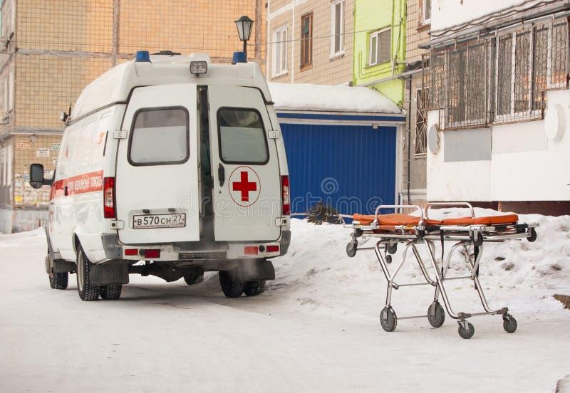 Medicinsk bår bredvid ambulansen med öppna dörrar på gatan nära ingången av bostads- byggnad - bild royaltyfria foton