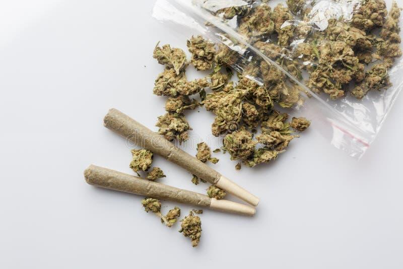 Medicinsk cannabis fogar ihop och knoppar spridda från packevit över royaltyfri fotografi