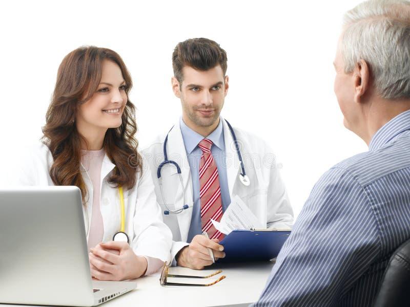 Medicinsk diskussion på sjukhuset med den äldre patienten royaltyfri bild