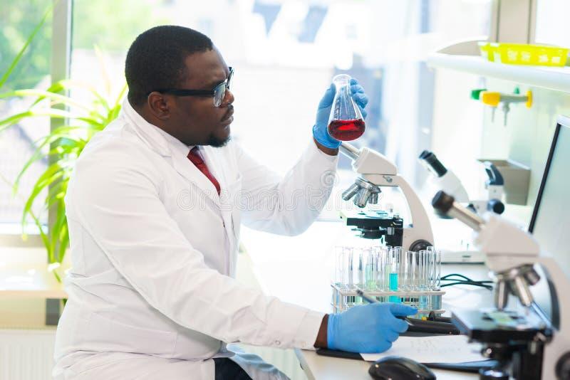 Medicinsk doktor för afrikansk amerikan som arbetar i forskninglabb Vetenskapsassistent som gör farmaceutiska experiment Kemi arkivbilder