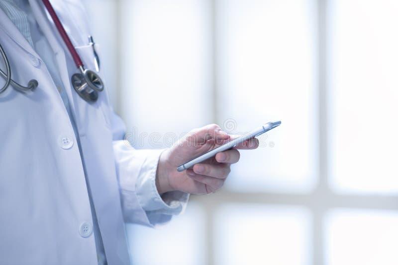 Medicinsk doktor som använder den smarta telefonen för arbete i sjukhus arkivfoton