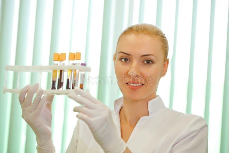 Medicinsk doktor som ser på provröret med blod arkivbild