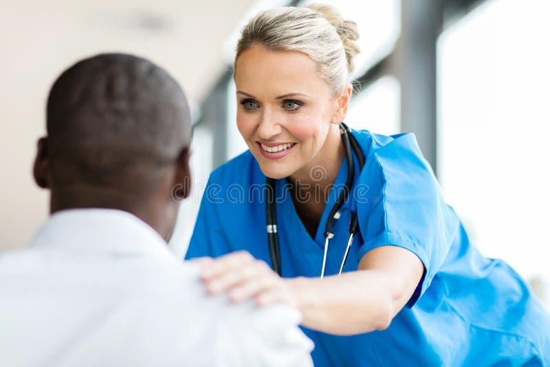 Medicinsk doktor som tröstar pateint arkivfoton