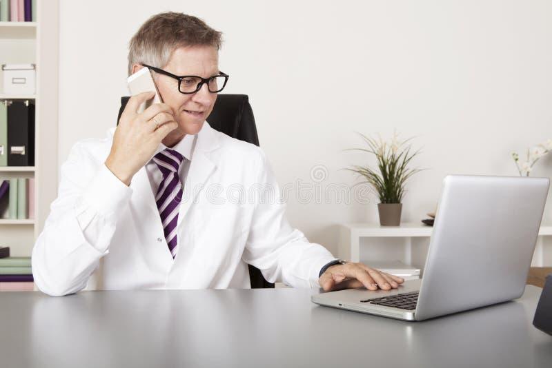Medicinsk doktor Using Mobile Phone och bärbar dator arkivbild
