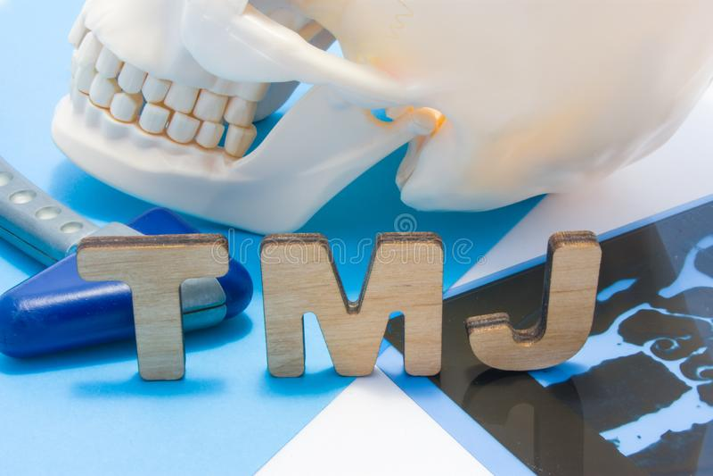 Medicinsk förkortning för TMJ av den temporomandibular skarven TMJ-bokstäver som omges av den mänskliga skallen med lägre käke, n royaltyfri fotografi