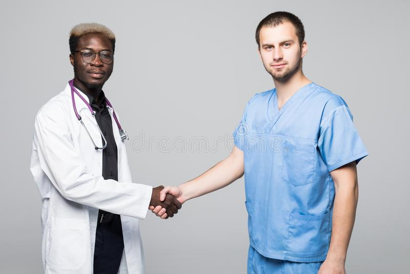 Medicinsk handskakning Doktors- möte Skakar det säkra anseendet för doktor två på grå färger och deras händer royaltyfri foto