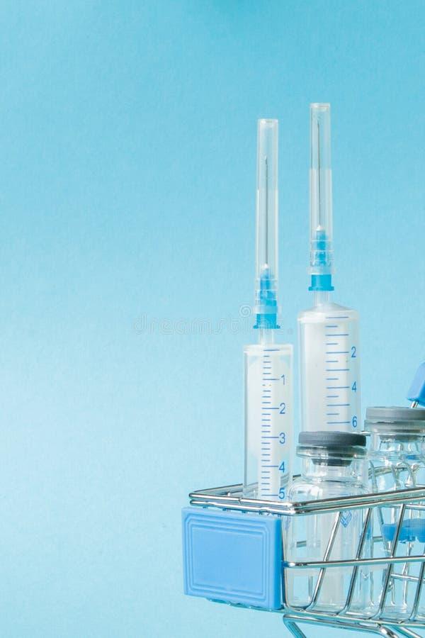 Medicinsk injektion, i att shoppa sp?rvagnen p? bl? bakgrund Id?rik id? f?r h?lsov?rdkostnad, apotek, sjukf?rs?kring och royaltyfri bild