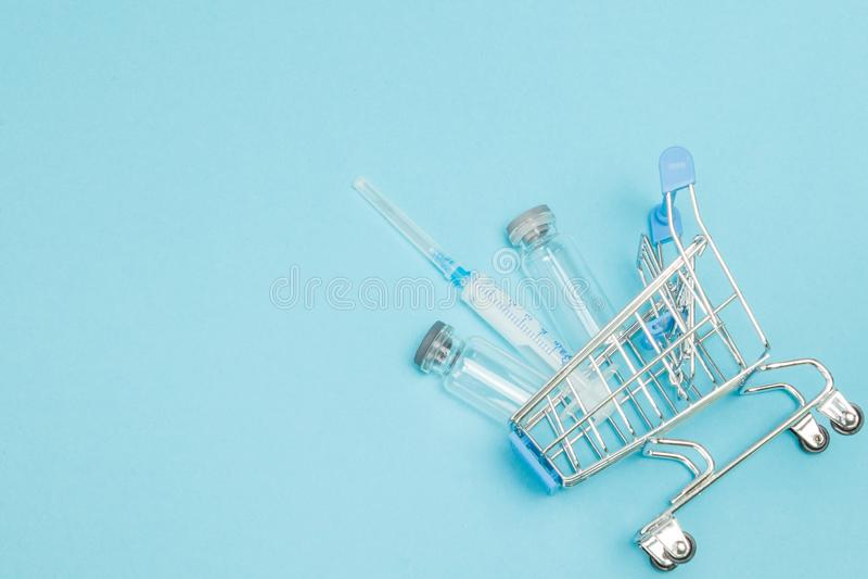 Medicinsk injektion, i att shoppa sp?rvagnen p? bl? bakgrund Id?rik id? f?r h?lsov?rdkostnad, apotek, sjukf?rs?kring och fotografering för bildbyråer