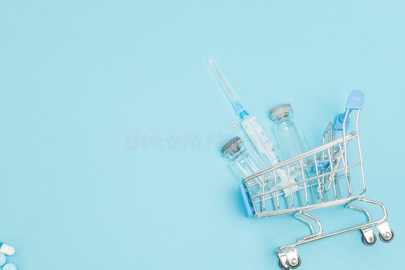 Medicinsk injektion, i att shoppa sp?rvagnen p? bl? bakgrund Id?rik id? f?r h?lsov?rdkostnad, apotek, sjukf?rs?kring och arkivfoton