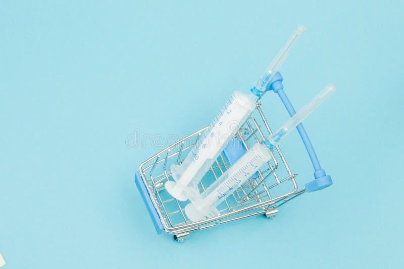 Medicinsk injektion, i att shoppa sp?rvagnen p? bl? bakgrund Id?rik id? f?r h?lsov?rdkostnad, apotek, sjukf?rs?kring och arkivfoto