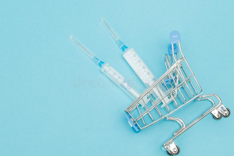 Medicinsk injektion, i att shoppa sp?rvagnen p? bl? bakgrund Id?rik id? f?r h?lsov?rdkostnad, apotek, sjukf?rs?kring och arkivbild