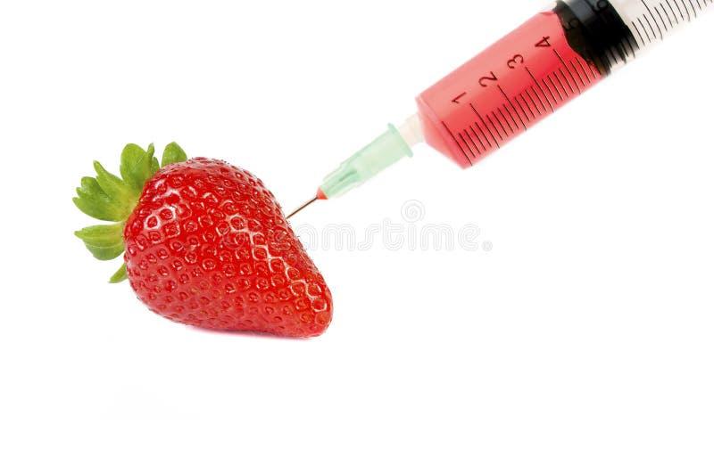 Medicinsk injektion med flytande och en röd jordgubbe arkivfoton