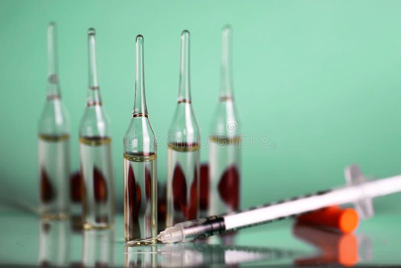 Medicinsk injektionsspruta för grön bakgrundsampull arkivbilder