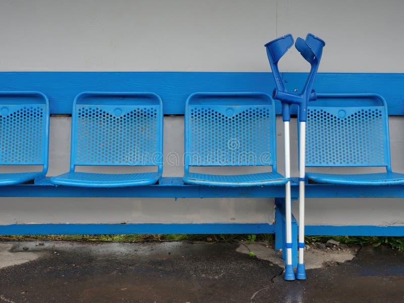 Medicinsk krycka på blåttmetallplatser på utomhus- stadionspelarebänk arkivfoton