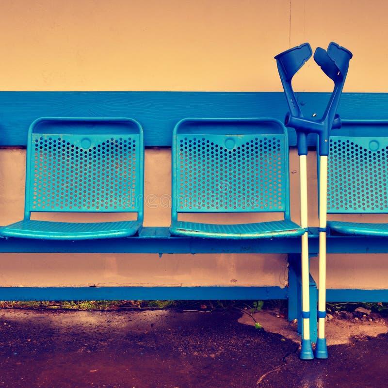 Medicinsk krycka på blåttmetallplatser på utomhus- stadionspelarebänk royaltyfri foto