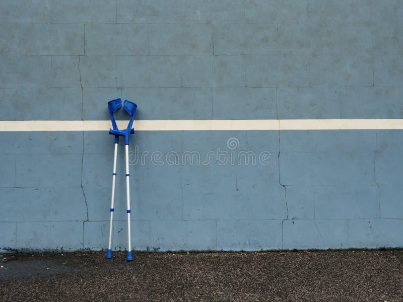 Medicinsk krycka på den blåa utbildningstennisväggen på den utomhus- stadionspelaredomstolen, arkivbilder