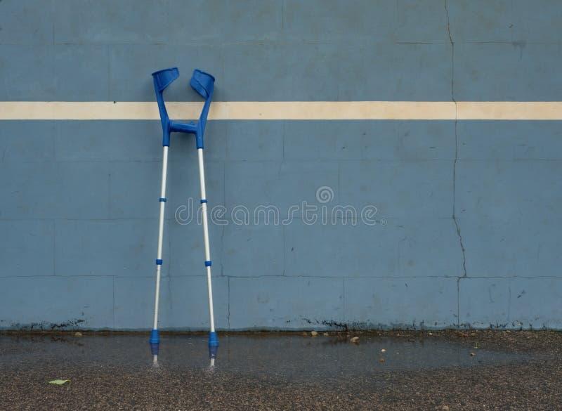 Medicinsk krycka på den blåa utbildningstennisväggen på den utomhus- stadionspelaredomstolen, arkivbild