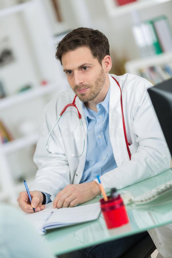 Medicinsk läkaredoktor som lyssnar till patienten och tar anmärkningar royaltyfria foton