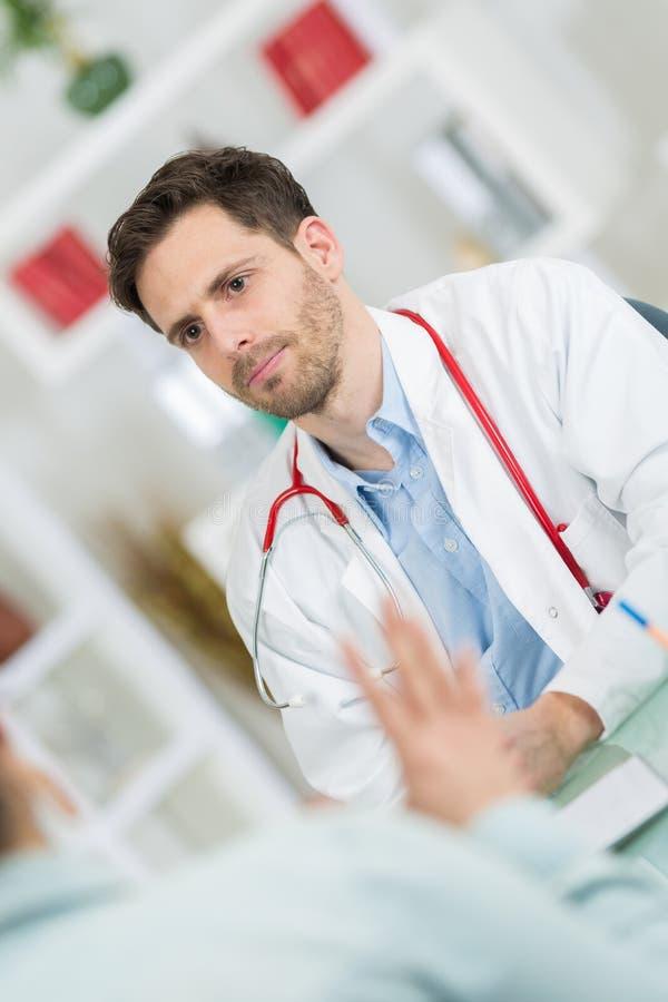 Medicinsk läkaredoktor som lyssnar till patienten och tar anmärkningar arkivbilder