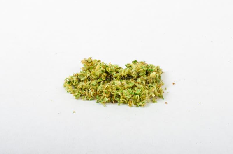 Medicinsk marijuana som malas upp och, ordnar till för att rulla Med en stålknopprackare arkivbild