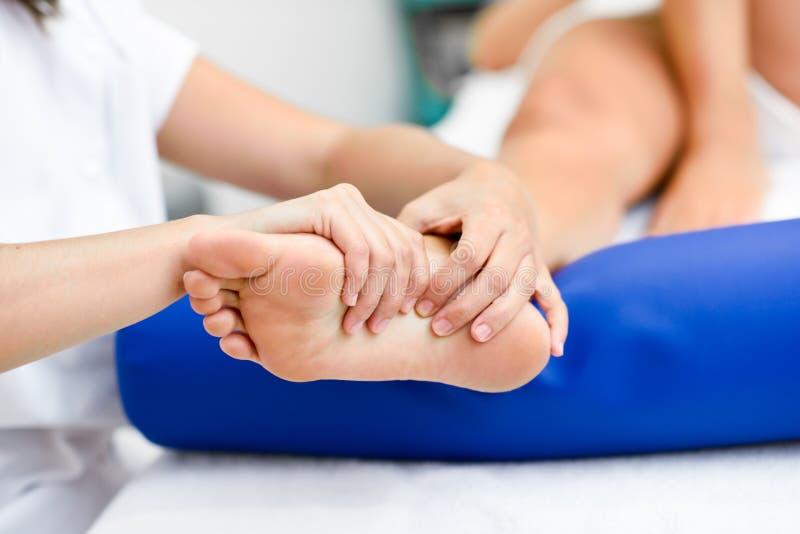 Medicinsk massage på foten i en sjukgymnastikmitt arkivfoton