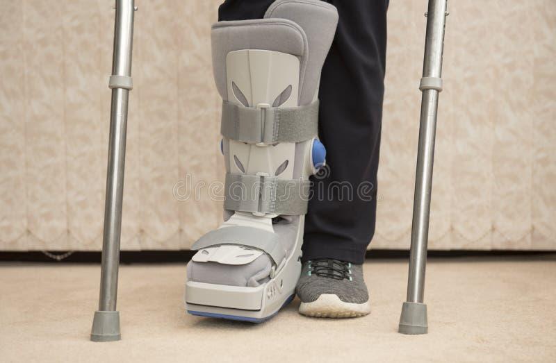 Medicinsk ortopedisk känga med cruches royaltyfri fotografi