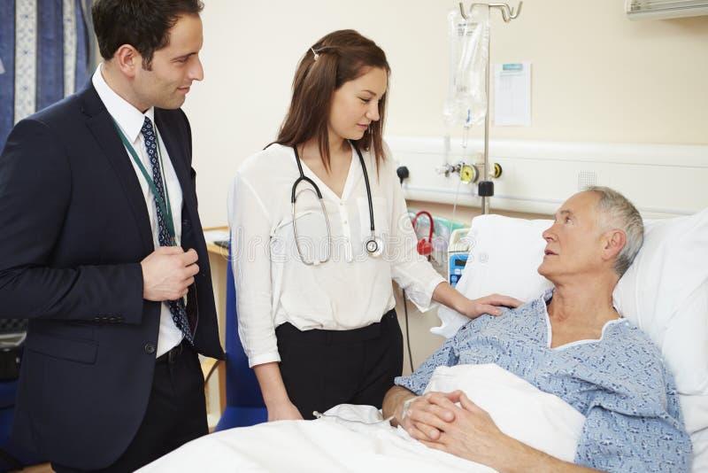 Medicinsk personal på rundor som står vid manlig patients säng fotografering för bildbyråer