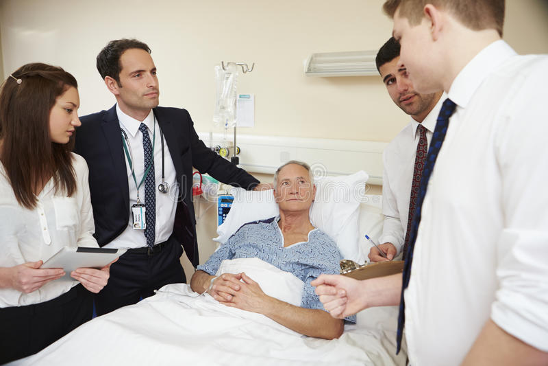 Medicinsk personal på rundor som står vid manlig patients säng royaltyfria bilder
